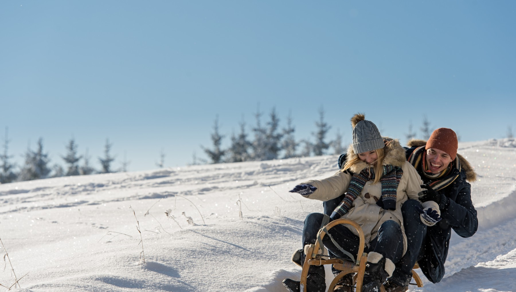 Young playful couple having fun in the snow sledging downhill_162833285