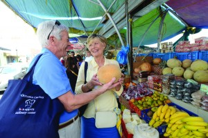 Couple choose fruit at a market on Oceania Cruises culinary tour